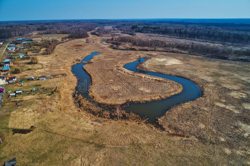 River bend in the shape of a horseshoe. The view from a great height. Early spring, landscape with dead grass stock image