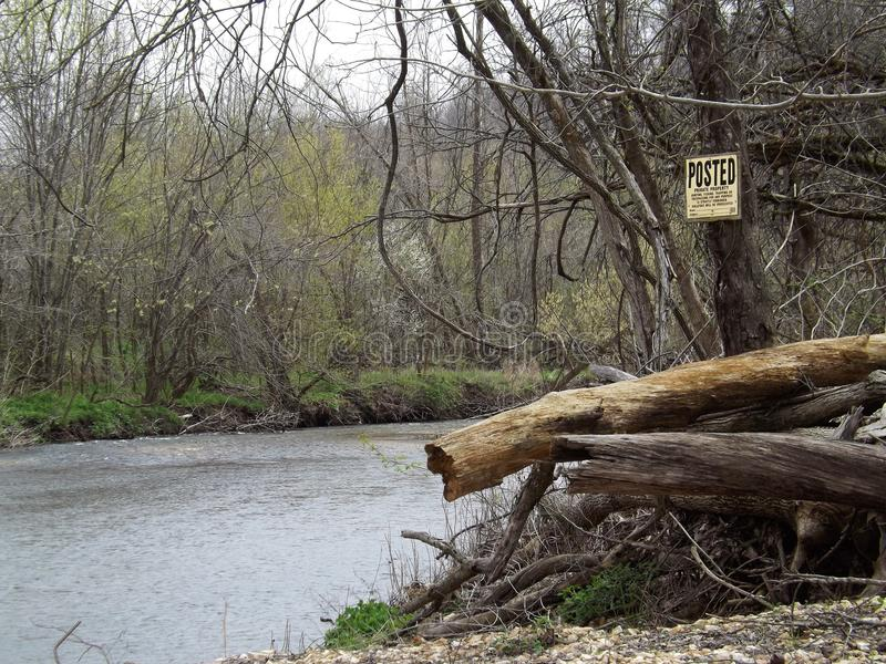 River bend. In the spring, with old sign, and drift wood stock photos