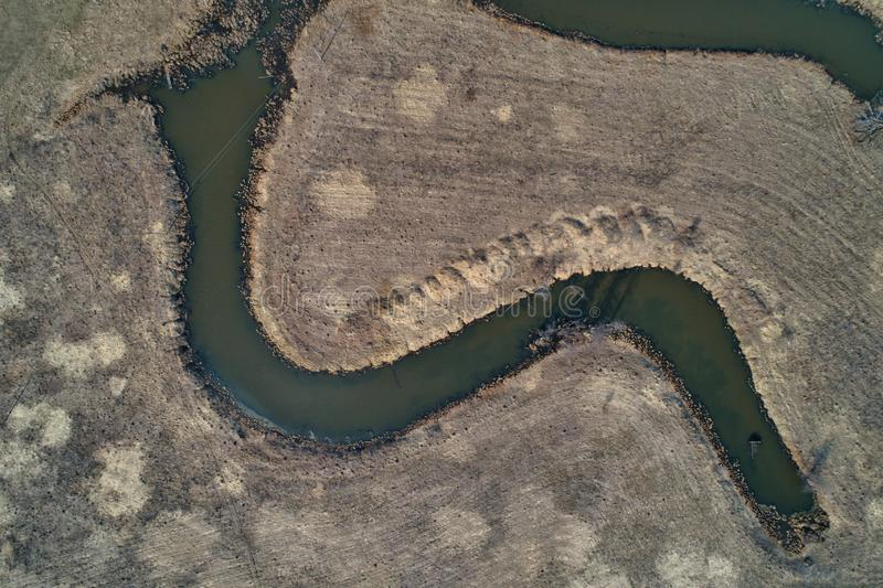 River bend, view from a great height. River bend. Aerial view. Early spring, landscape with dead grass stock images