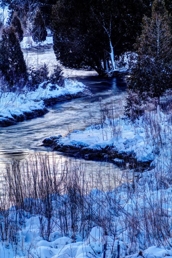 River Bending Through Cedars On A Snow Covered Early Morning. The Waters of the Credit River twist between the cedar trees and the snow covered ground in early stock images