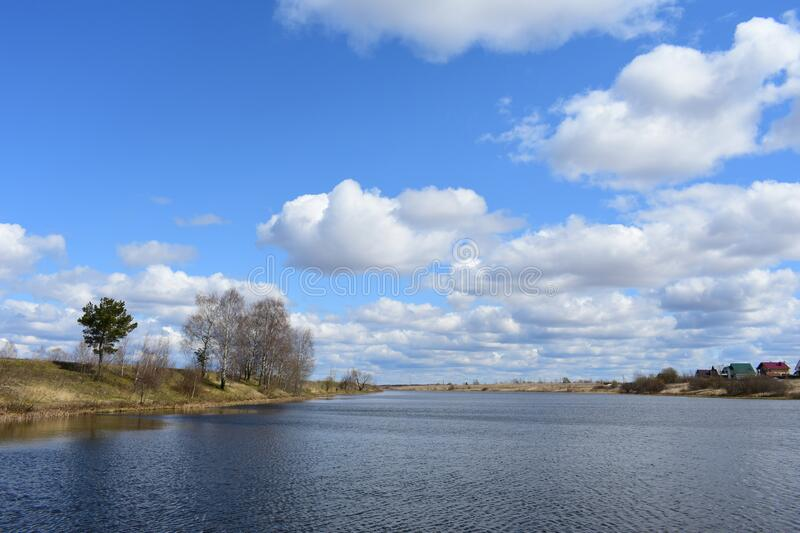 River, birch, pine. On the high banks are village houses, trees and green grass. There are white clouds in the blue sky. Wind. Forms waves over the water stock photos