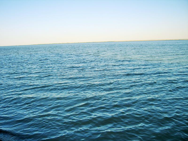 River and blue sky separated by a horizon line. Blue river and blue sky separated by a horizon line royalty free stock image