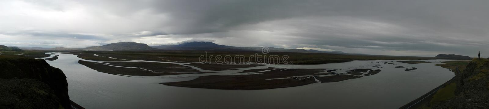 River in Central Iceland. Man overlooking the River in Central Iceland (180 degree panorama) Vatnajokul and Mt. Hekla in the clouds stock photography