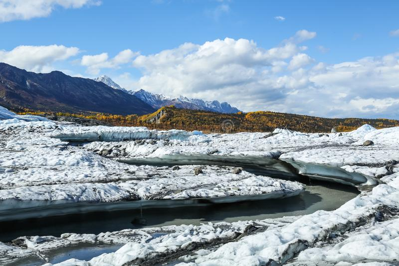 River channel melted into the Matanuska Glacier in Alaska. Yellow leaves of autumn coat the background stock images