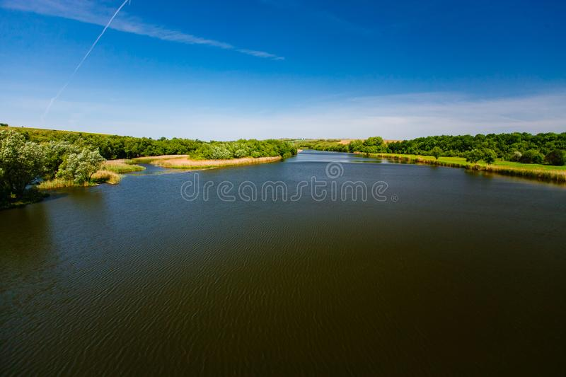 River creek surrounded by green woods. Water landscape royalty free stock image