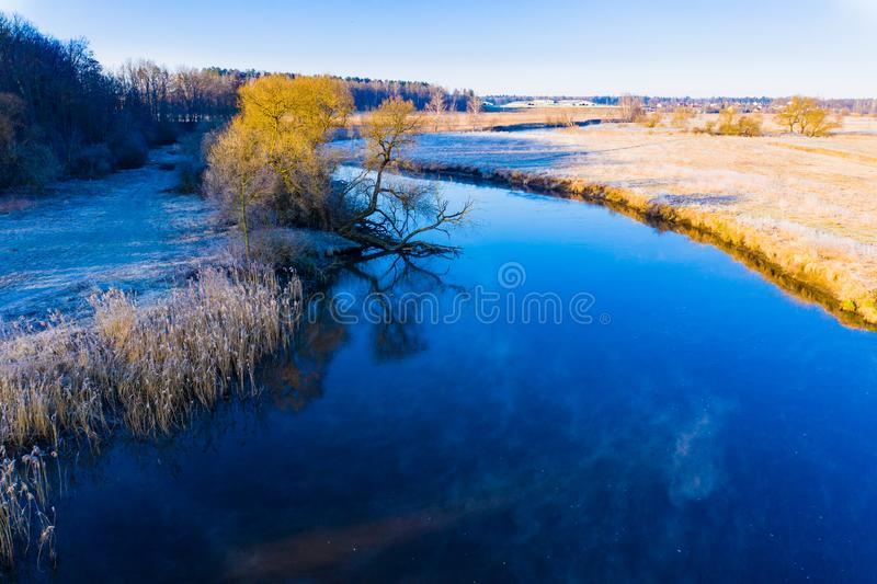 River curve in cold season. Beautiful rural landscape. Sun shining bright in countryside. River curve in cold season. Beautiful rural landscape. Sun shining stock photo