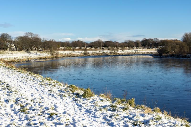 River Dee shores with green grass covered by snow during winter, Aberdeen, Scotland stock photography