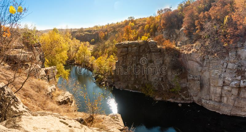 River in a delightful autumn forest at sunny day. Autumn forest landscape among yellow and orange trees, beauty of nature royalty free stock photo