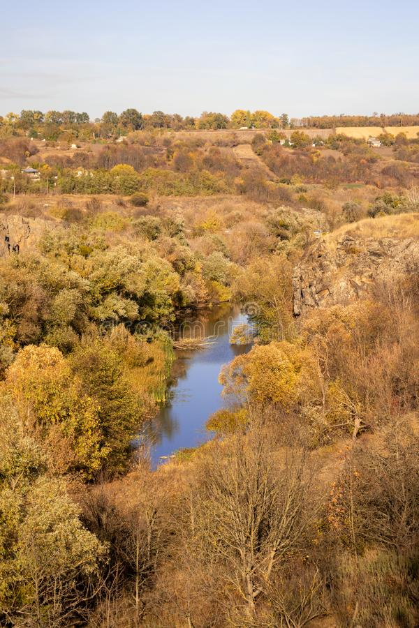 River in a delightful autumn forest at sunny day. Autumn forest landscape among yellow and orange trees, beauty of nature stock image