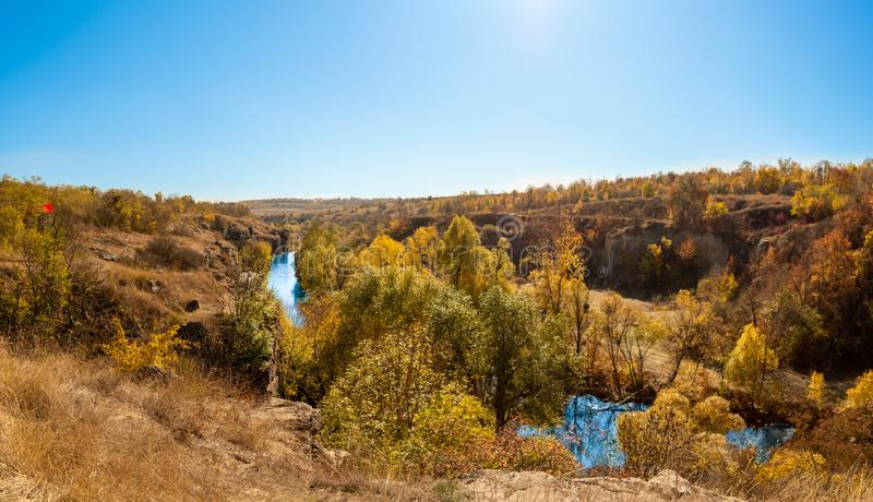 River in a delightful autumn forest at sunny day. Autumn forest landscape among yellow and orange trees, beauty of nature royalty free stock images