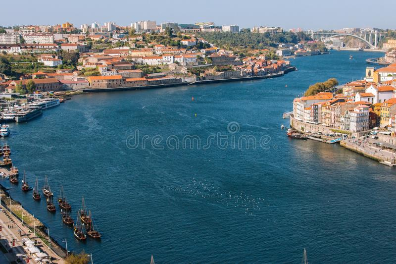 River Douro with embankment of Porto and boats. Old buildings with brick roofs by river Douro in Porto, Portugal. River Douro with embankment of Porto and boats royalty free stock images