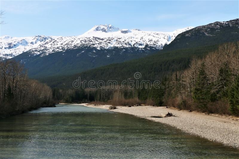 River in Dyea, Alaska with snow covered mountains. River in Dyea, Alaska, where historic Yukon gold rush Chilkoot Trail begins. March 2019 royalty free stock images