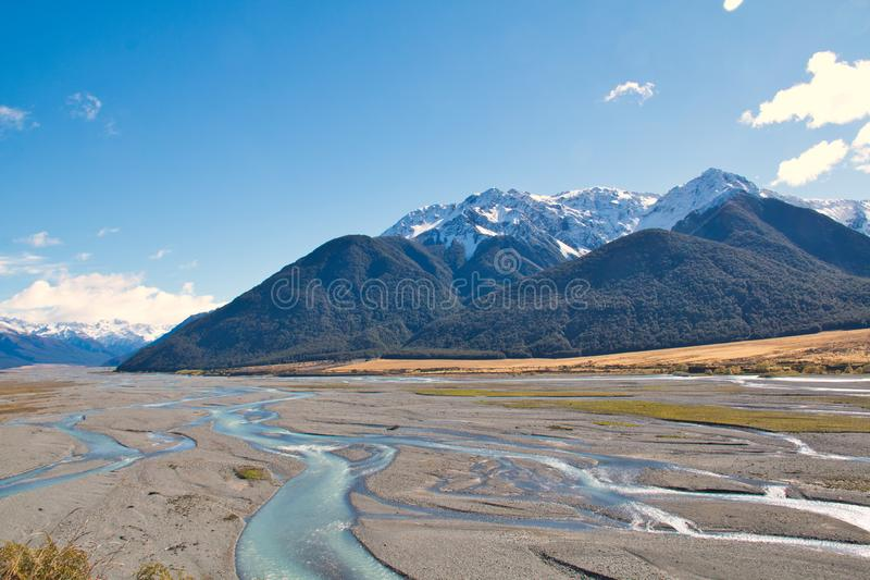 A river threads its way between the peaks of snow-capped mountains royalty free stock photos