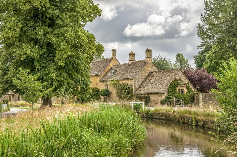River Eye at Lower Slaughter. River Eye and reeds with historic stone cottages at Lower Slaughter, in the English Cotswolds, said to be one of the prettiest royalty free stock photography