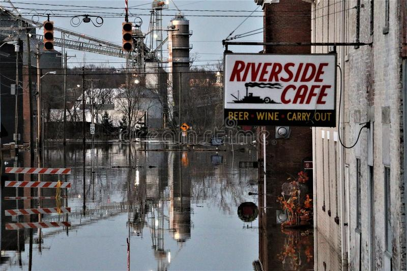 River flood up street in Aurora, Indiana at evening. February 2018 flooding of Aurora, Indiana from the Ohio River. River flooding road to restaurant stock photo