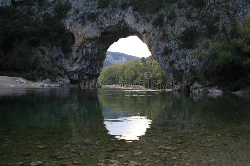 Natural formed bridge of stones and rocks over a river. River flooding under a natural formed bridge of rocks and stones stock image