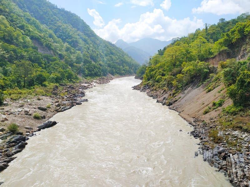 River flow between green mountain stock photo