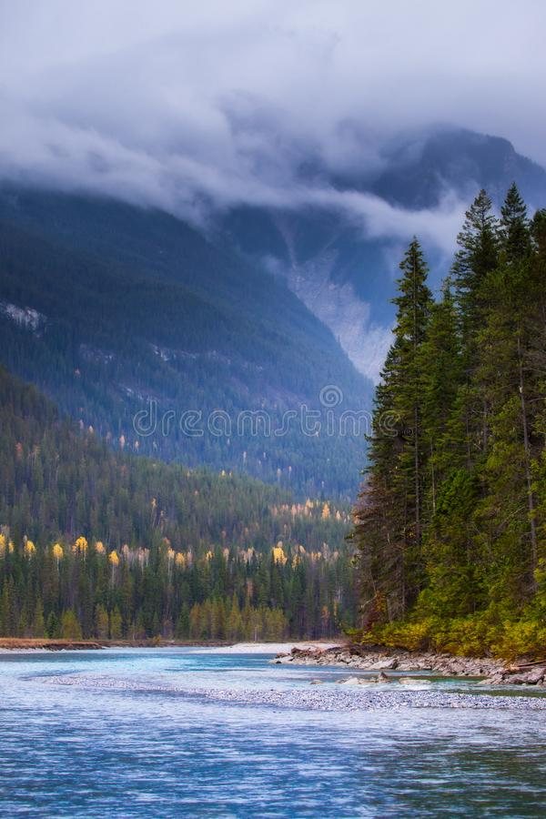 A river flowing through the mountains on a cloudy stormy day royalty free stock images