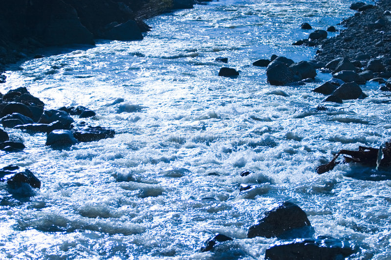 River flowing over rocks. With white water stock image