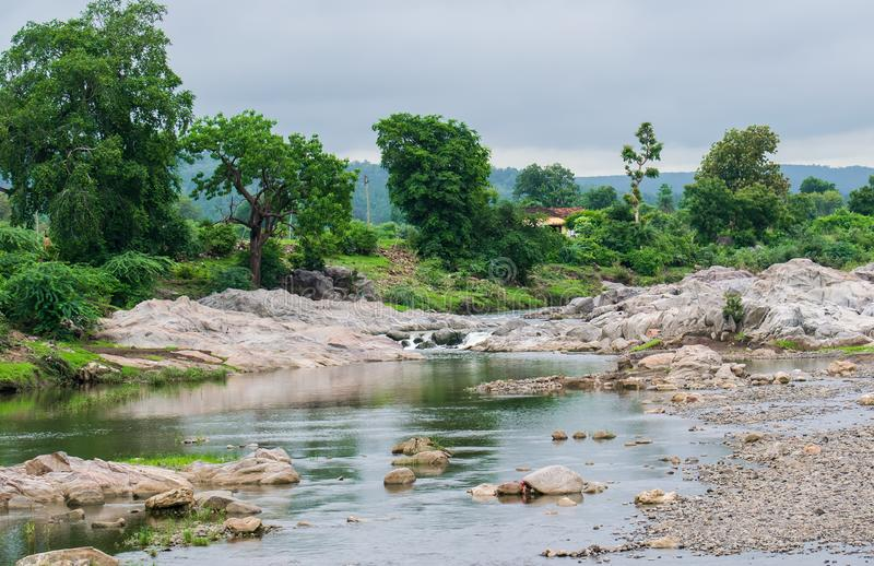 River in monsoon. River flowing through the rocks in monsoon season , trees and a hill seen in background royalty free stock images
