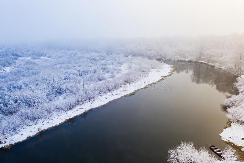 River flows along winter forest on foggy morning. Season concept. Aerial landscape. River flows along winter forest on a foggy morning. Season concept. Aerial royalty free stock image