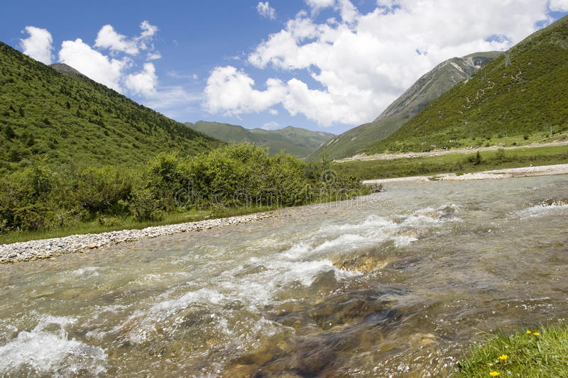 River flows in mountain against blue sky
