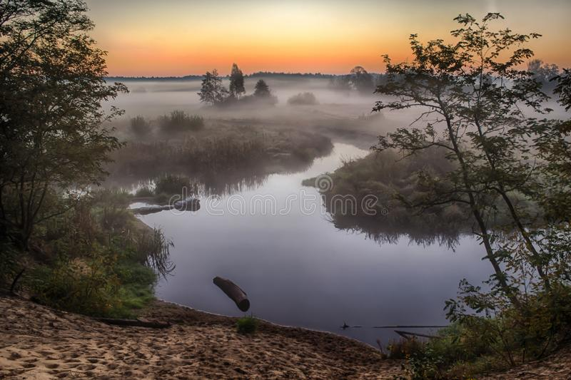 River in the fog, just before sunrise. A warm glow in the clouds from the first rays of the sun. royalty free stock photos