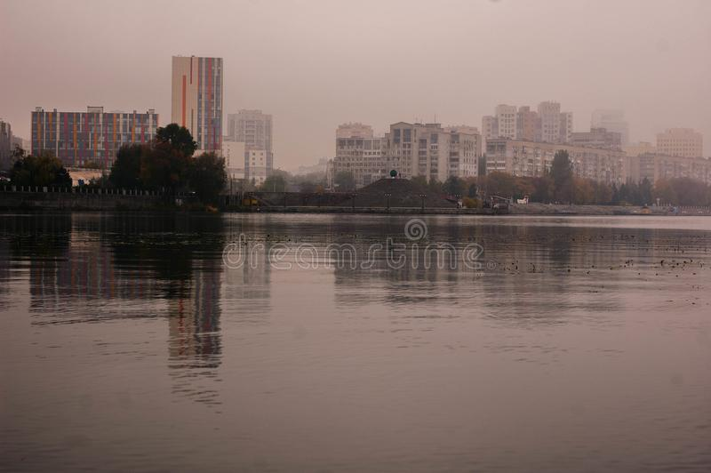 The river in the fog with the reflection of the city on the water. Surface in autumn stock image