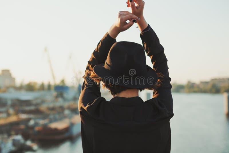 River and girl under bridge. Emotioanl hands up. Girls back uotside portrait royalty free stock images