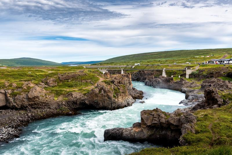 A river from Godafoss Falls, Akureyri, Iceland, surrounded by huge rocks and a concrete bridge. A horizontal shot of a river from Godafoss Falls, Akureyri stock images