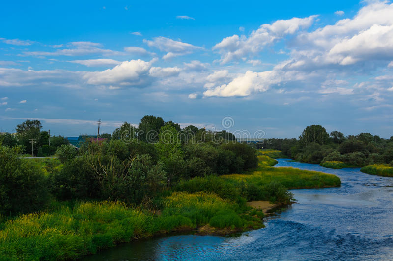 River with grass and blue sky with clouds stock photo
