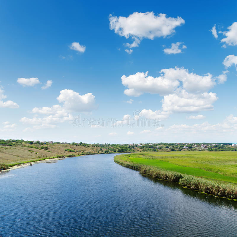 River in green landscape under white clouds in blue sky stock photography