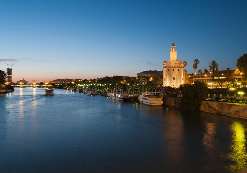 River Guadalquivir in Seville and Golden Tower. View of river Guadalquivir in Seville, Spain with Golden Tower (Torre del Oro) and Triana bridge at night royalty free stock photos