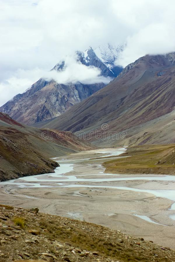 The river has almost dried up in the mountains. Snow peaks on background royalty free stock images