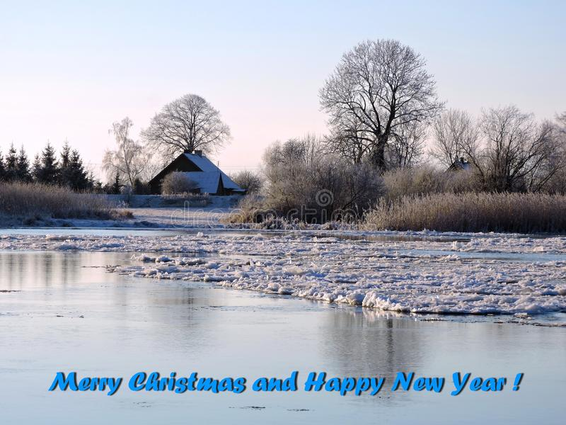 River in ice and words - Marry Christmas and happy New Year, Lithuania. River Atmata in ice, trees and home and greeting words - Merry Christmas and Happy New royalty free stock photography