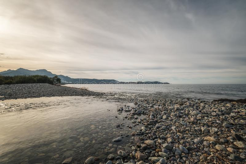 River joins the sea on a pebble beach in Corsica stock photo