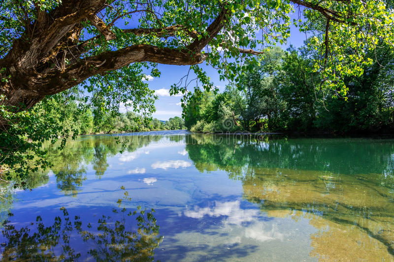 River Kolpa. Kolpa river with reflections and shadows landscape in the water. Clear water and blue sky with clouds stock photography