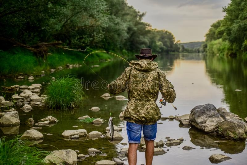 River lake lagoon pond. Trout farm. Fisherman alone stand in river water. Fisherman fishing equipment. Hobby sport. Activity. Man bearded fisherman. Fish stock image