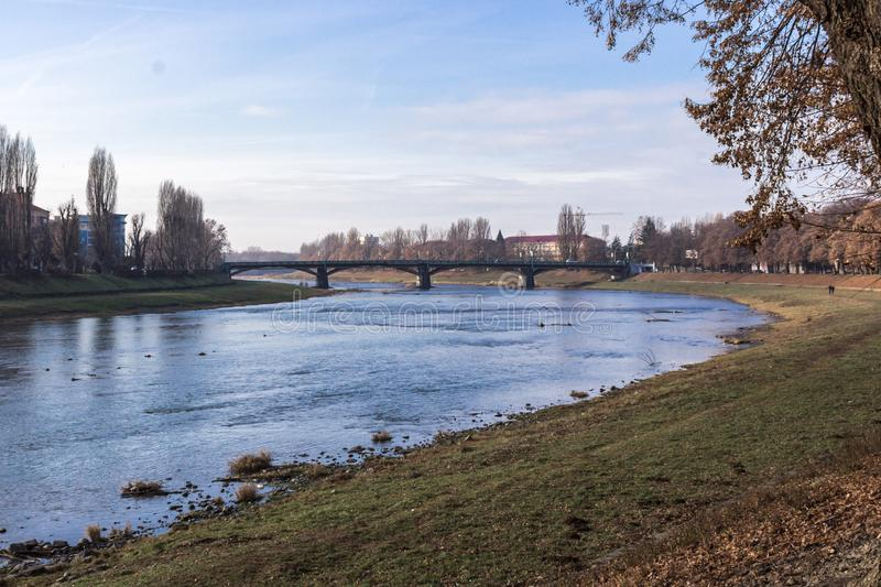 Bridge over the river in the city. River landscape in spring or autumn. The bend of a shallow river. Trees on the bank along the river. Picturesque autumn stock images
