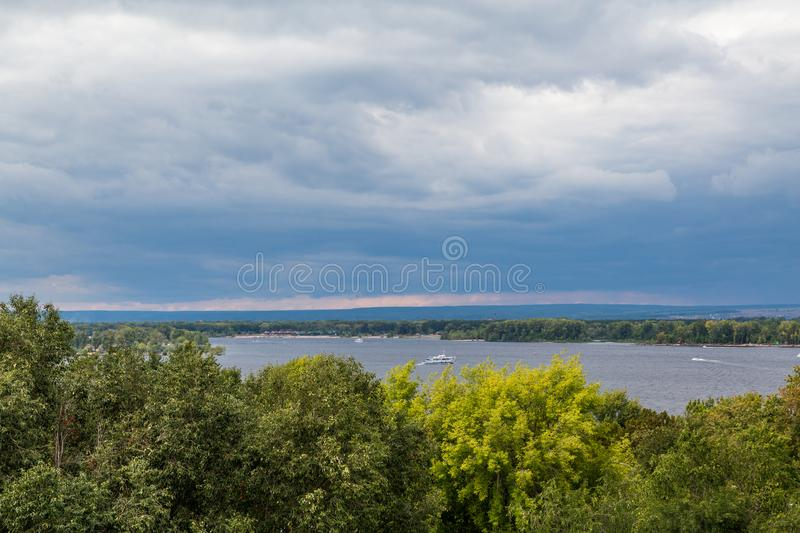 A river landscape. Summer or autumn. Tourist boats. The river Volga in the city Samara, Russia. Heavy clouds in the evening. Sunset royalty free stock photo