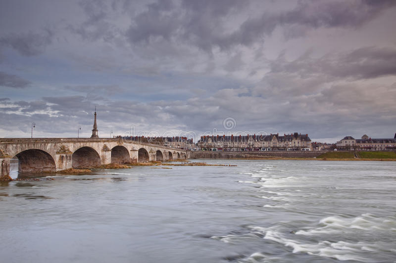 River Loire and Blois. The fast flowing water of the Loire. The bridge to the left is Pont Jacques Gabriel. This scene can be seen at the town of Blois in France royalty free stock image