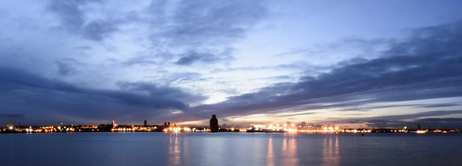 River Mersey and Birkenhead by night - panoramic view from Keel Wharf waterfront in Liverpool, UK. River Mersey and Birkenhead by night - panoramic view from royalty free stock image