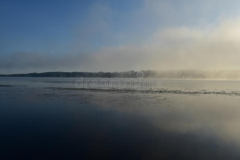 River morning fog at sunrise over the water, on the coast of the forest stock photo