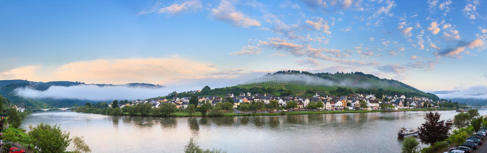River Moselle panorama in Zell an der Mosel. Beautiful 180 degree panoramic sunrise view of the river Moselle at the small wine growing town Zell an der Mosel on royalty free stock photo