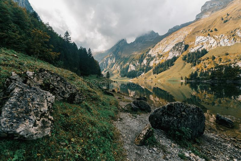 River Between Mountains Under Cloudy Sky stock photo