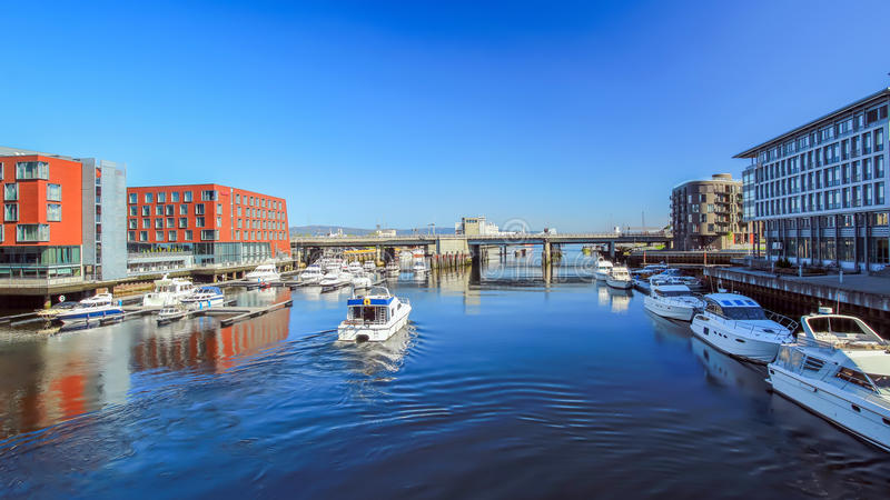 River Nidelva in Trondheim, Norway. View of the river Nidelva with boats, bridge and buildings in Trondheim, Norway royalty free stock photos