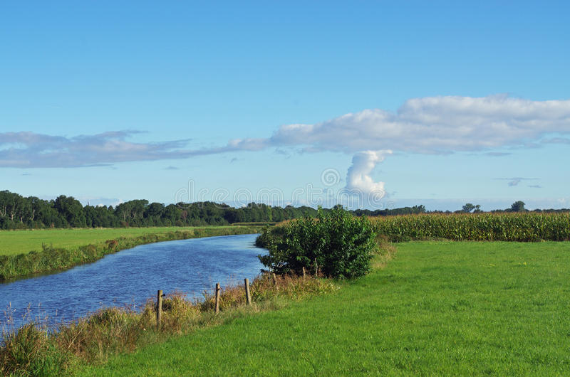 River in open landscape, field with grass, trees and blue sky in the Netherlands. Nature reserve Drenthe royalty free stock image