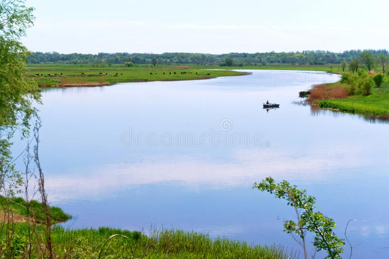 A winding river, a river with overgrown banks, a lonely boat on a wide river royalty free stock image