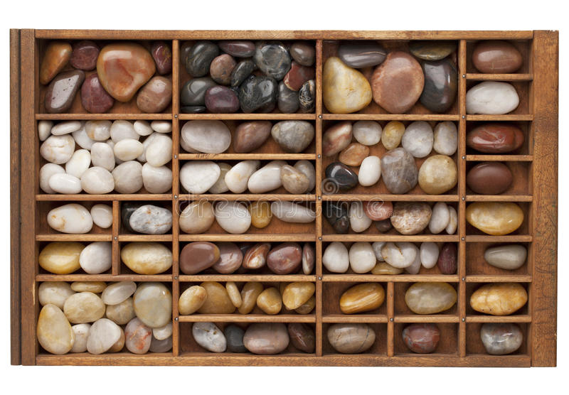 River pebbles in typesetter drawer. Colorful river pebbles in vintage wood typesetter drawer isolated with clipping path royalty free stock images