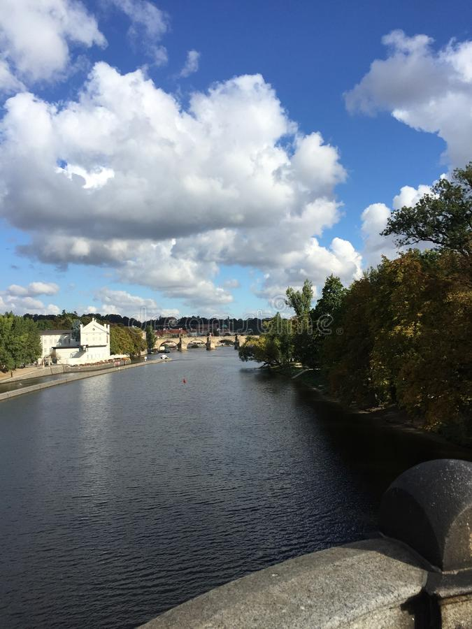 River in Prague. View from a bridge in Prague looking out onto the river , another bridge off into the distance and beautiful white fluffy skies stock photography
